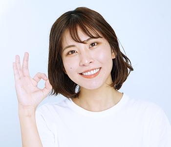 女性が手でOKマークを作って笑っている写真